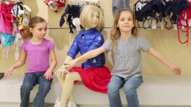 Mannequin in clothes between two girls — Stockvideo
