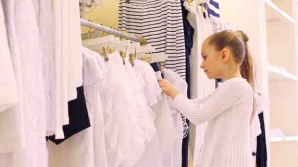 Chica escoge la ropa en tienda — Vídeo de stock