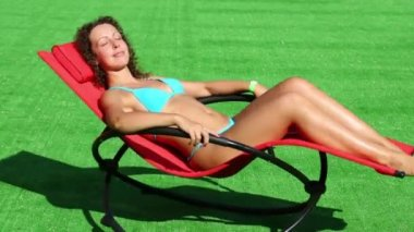Woman in swimsuit swings in red chair — Stock Video