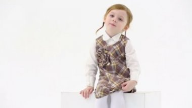 Little girl sits on white cube — Stock Video