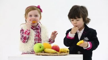 Little boy and girl eat oranges — Stock Video