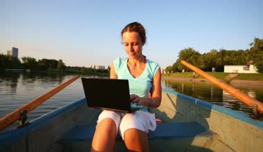 Woman sits in boat with laptop — Stock Video