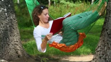 Young girl in hammock and reading book — Stock Video