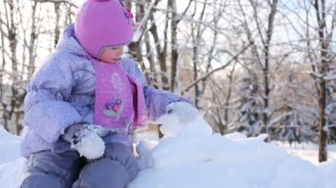 Little girl sits on snowdrift and plays — Stock Video