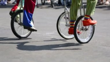 Feet of clowns riding on unicycles outdoor — Stock Video