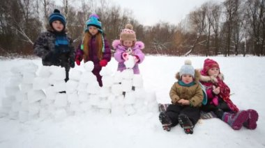Children building wall from snow blocks — Stock Video