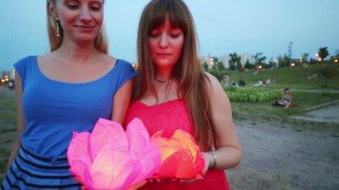 Two girls hold at water lanterns — Stok video