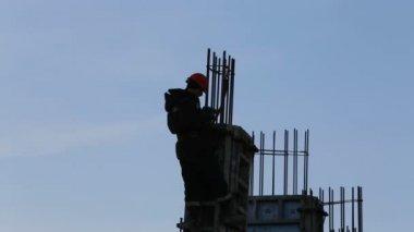 Silhouette of builder installs rebar on construction — Stock Video