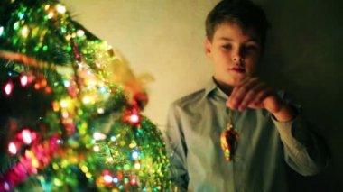 Handsome boy decorates Christmas tree — Stock Video