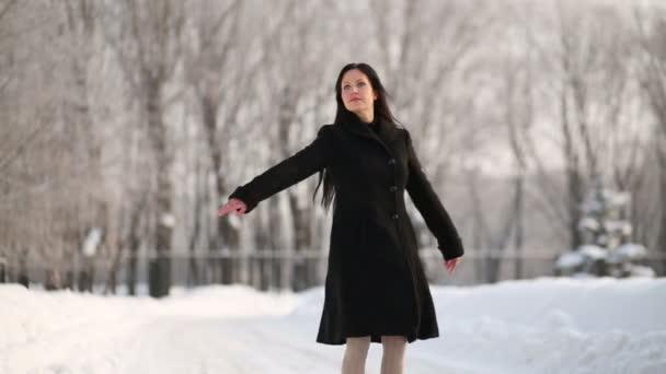 Mujer joven en danzas de capa negra — Vídeo de stock
