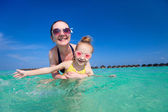 Mother and daughter at tropical beach — Stock Photo