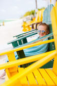 Little girl relaxing in colorful chair at beach — Stock Photo