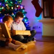 Kids at home on Christmas eve opening gifts — Stock Photo #52827763