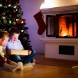 Kids at home on Christmas eve opening gifts — Stock Photo #54223473