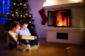 Kids at home on Christmas eve opening gifts — Stock Photo
