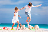 Two kids crushing sandcastle — Stock Photo