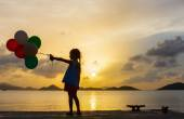 Happy girl with balloons at sunset — Stock Photo