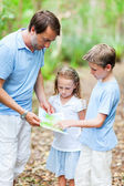 Father and kids with map hiking — Stock Photo