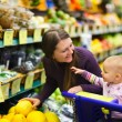 Mother and baby daughter in supermarket — Stock Photo #62633679