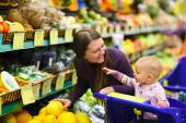 Mother and baby daughter in supermarket — Stock Photo