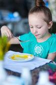 Little girl eating breakfast — Stockfoto