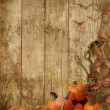 Autumn leaves and pumpkins on a wooden background — Stock Photo #53783335