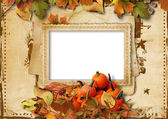 Pumpkins, autumn leaves and frame for photo on vintage backgroun — Stock Photo