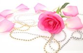 Pink rose and beads — Stock Photo