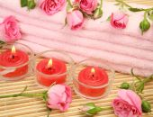 Pink towel and candles with roses — Stock Photo