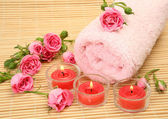 Pink towel and candles with roses — Stockfoto