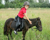 Girl rides pony on field — Stock Photo