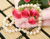 Red roses, beads and towel — Stock Photo