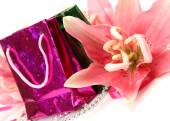 Gifts and pink lilies — Stock Photo