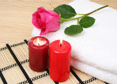 Rose on towels with burning candles — Stock Photo