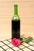 Wine and pink rose — Stock Photo
