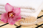 Bath towels,comb and orchid flower — Stock Photo