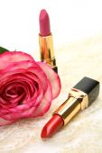 Red and pink lipsticks with rose — Stock Photo
