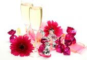 Gerbera with candies and glasses of champagne — Stock Photo