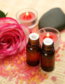 Aromatic oil and rose and candles — Stock Photo