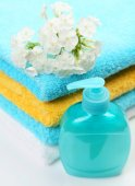 Towels with body care lotion — Stock Photo