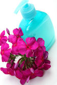Bottle for body care with pink flower — Stock Photo