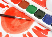 Brushes and paints with drawn sun — Stock Photo