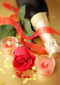 Champagne,red rose,burning candles and ribbon — Stock Photo