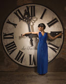 Woman on the background of a large clock face — Photo