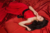 Fashionable brunette in a long red dress — Stock Photo