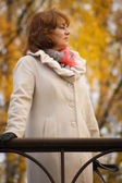 Elegant middle-aged woman in the autumn park — Stock Photo