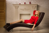 Beautiful lady in a red dress sitting on the couch — Stock Photo
