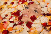 Beautiful sexy woman in bath with flowers petals — Stock Photo