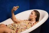 Beautiful sexy woman in bath with flowers petals while using the — Stock Photo