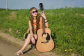 Young hippie girl sitting on a summer field with her guitar — Stok fotoğraf